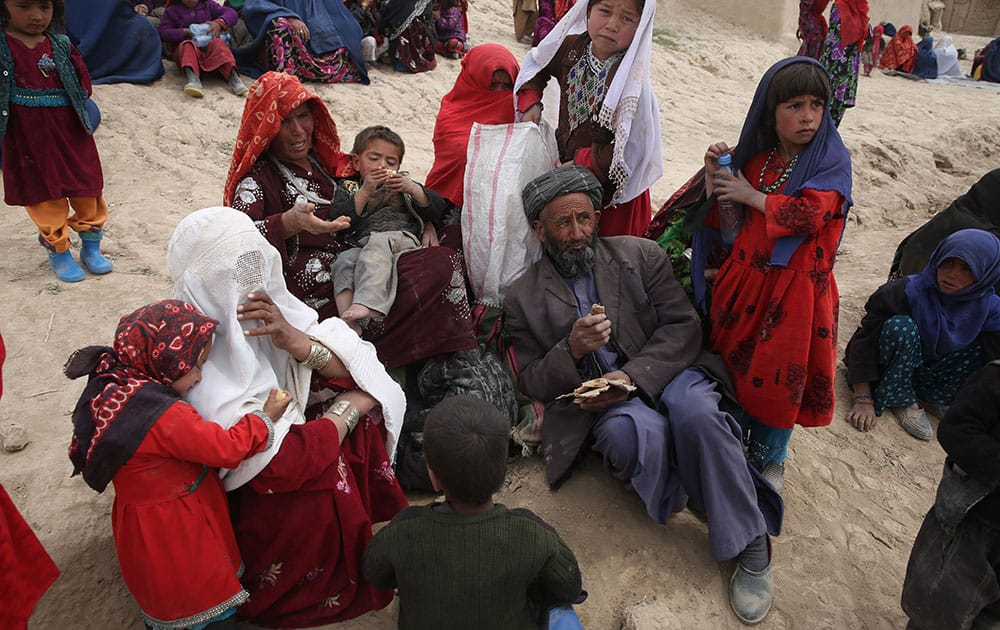 Survivors wait to receive donations near the site of Friday`s landslide that buried Abi-Barik village in Badakhshan province, northeastern Afghanistan.