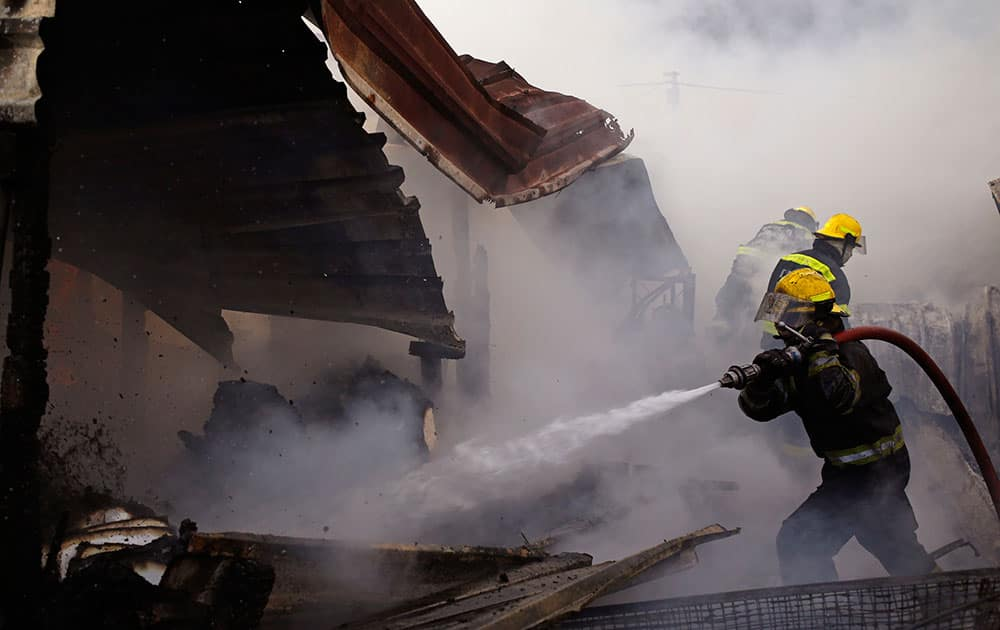 Firemen work to stop a Shack fire that destroyed up to twenty homes in Gugulethu township on the outskirts of the city of Cape Town, South Africa.