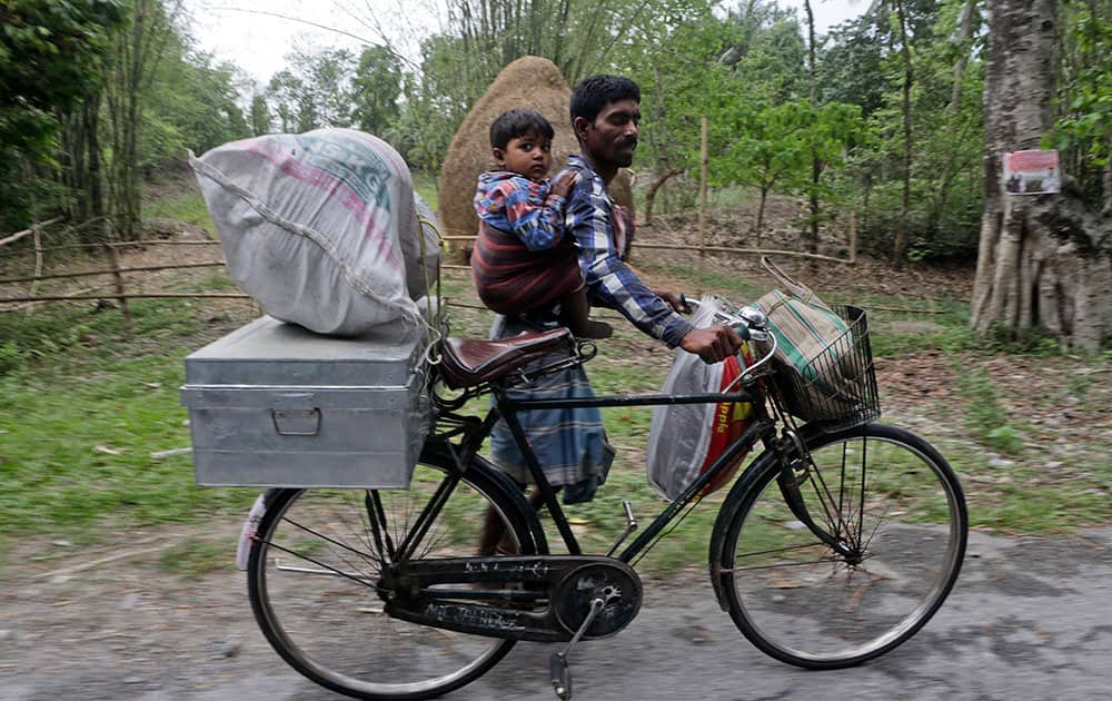 A villager carries a child and pushes a bicycle with his belongings to flee ethnic violence in Narayanguri village, in the northeastern Indian state of Assam.
