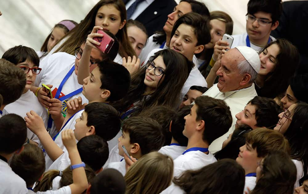 Pope Francis poses for a picture with children, at the end of a meeting with an Italian catholic group, in the Paul VI hall at the Vatican.