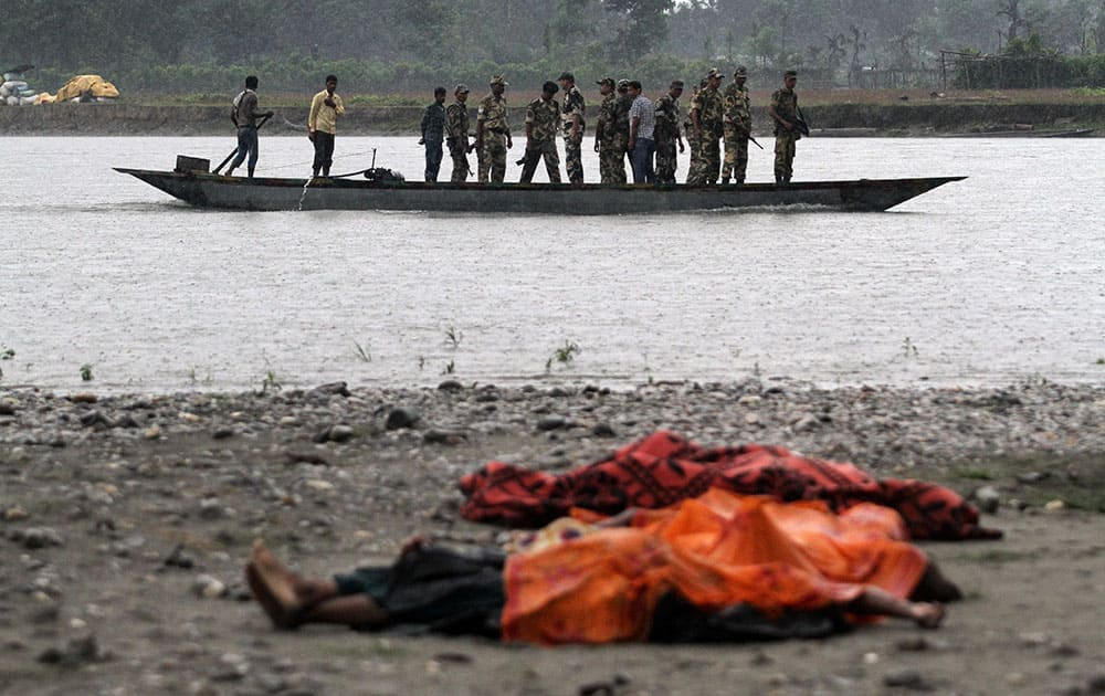 Bodies of victims killed in ethnic violence lie covered on the banks of the River Beki, as security officers patrol the area on a boat at Khagrabari village, in the northeastern Indian state of Assam.