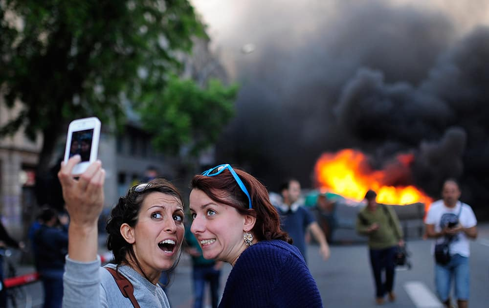 Tourists take a `selfie` picture as demonstrators burn a trash container during a May Day rally in Barcelona, Spain. Tens of thousands of workers marked May Day in European cities with a mix of anger and gloom over austerity measures imposed by leaders trying to contain the eurozone`s intractable debt crisis.