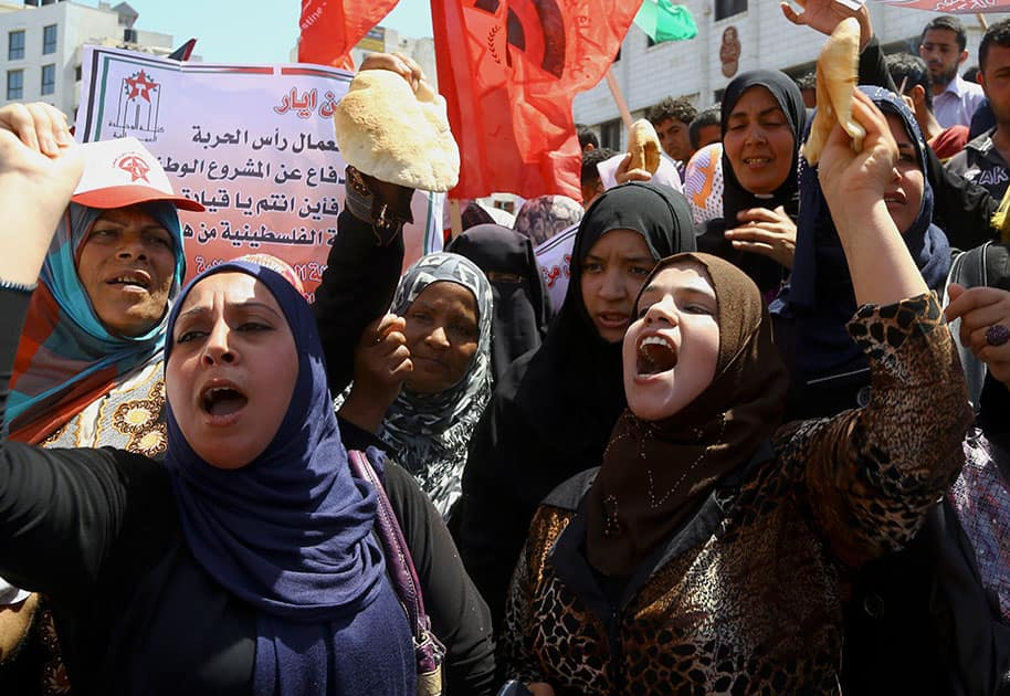 Palestinian labors hold loaves of bread while chanting slogans during a march for the International Labor Day at the Palestine square in Gaza City, northern Gaza Strip.