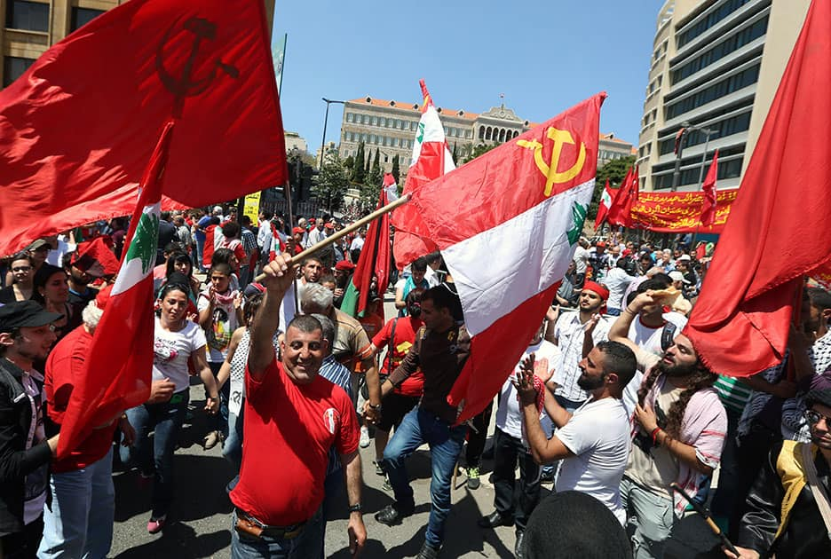 Supporters of the Lebanese Communist Party dance as they hold Lebanese and Communist Party flags during a demonstration to mark Labor Day in Beirut, Lebanon.