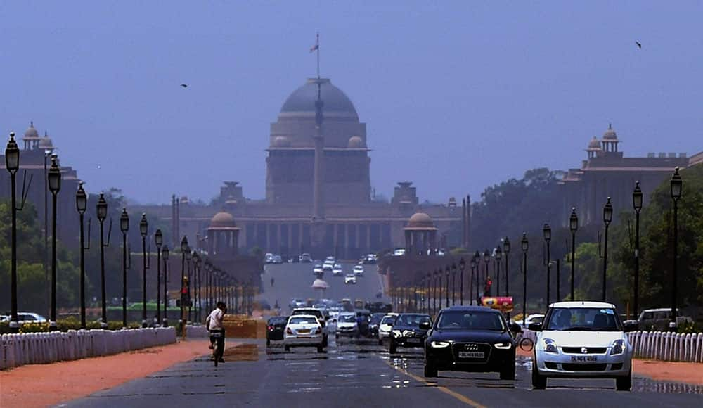 Mirage appears at Rajpath as vehicles move, on a hot day in New Delhi.