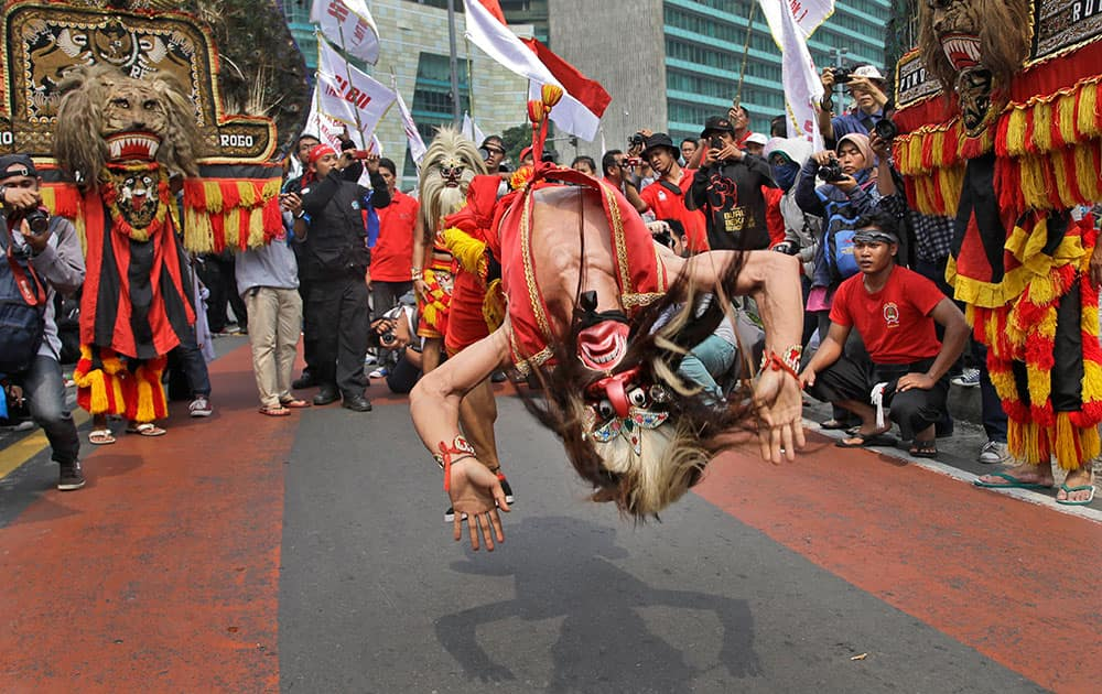 A masked dancer somersaults as he performs during a May Day rally in Jakarta, Indonesia.