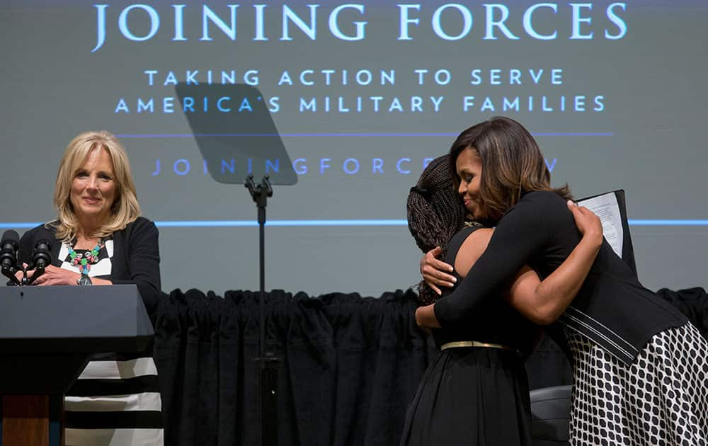 First lady Michelle Obama hugs Chrissandra Jackson accompanied by Dr. Jill Biden, at the third anniversary of Joining Forces, at the American Red Cross Hall of Service in Washington. Mrs. Obama announced pledges in excess of $150 million from foundations and corporations to help veterans and their families get the services they need in the places where they live as the country adjusts to a postwar footing. Jackson is a daughter of a military family.