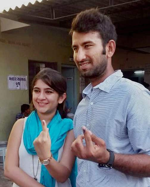 Cricketer Cheteshwer Pujara and his wife Puja display their inked fingers after casting votes for Lok Sabha elections in Rajkot.