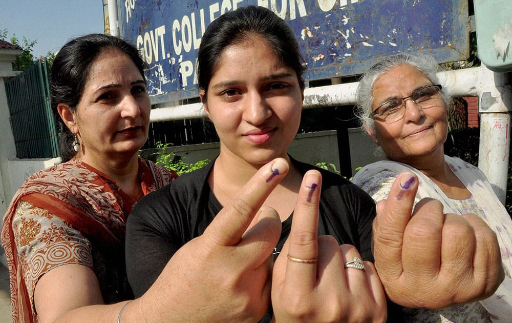 A girl, her mother and grandmother show their inked fingers after casting their votes at a polling station in Patiala.