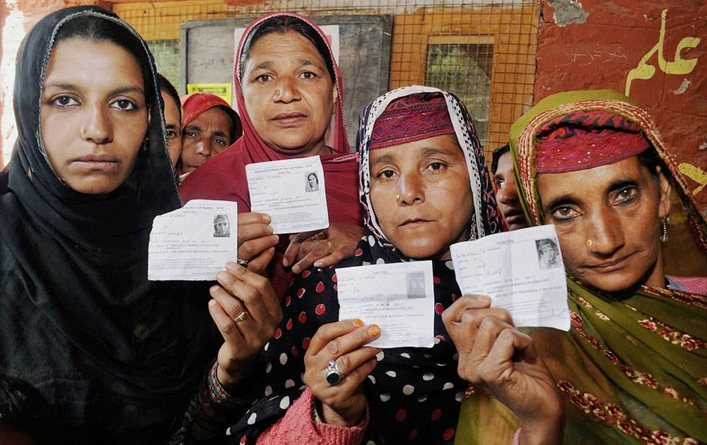 Kashmiri women show their voter cards as they stand in a queue to cast their votes at a polling station in Ganderbal.