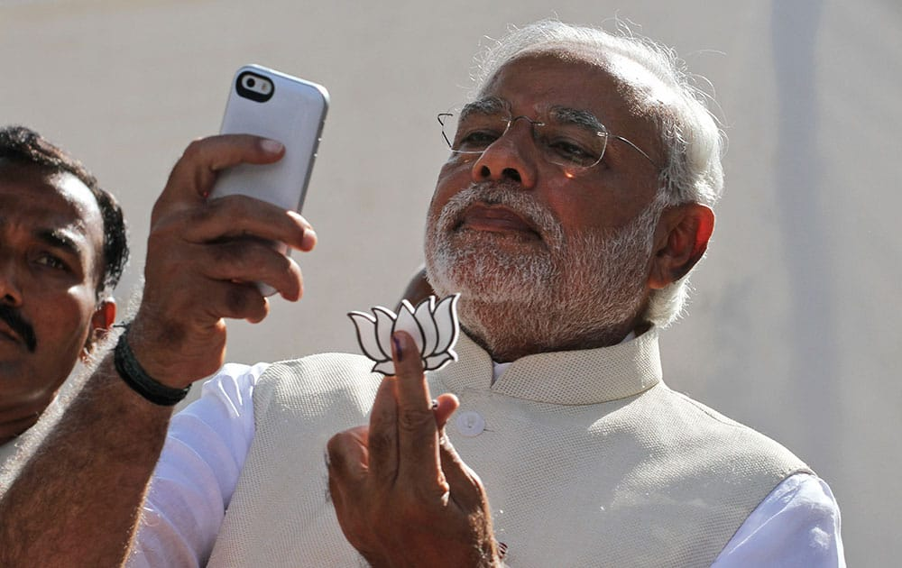 Bharatiya Janata Party's prime ministerial candidate Narendra Modi holds his party's symbol and looks into his phone after casting his vote in Ahmedabad.