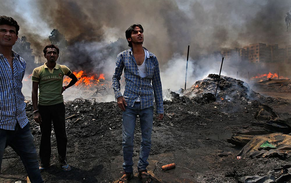 People watch a fire at a warehouse storing leftover cloth strips in New Delhi.