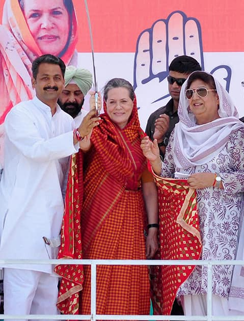 Congress President Sonia Gandhi is presented a sword by party candidate Vijay Inder Singla as party leader Rajinder Kaur Bhattal and others look on during an election rally in Barnala.