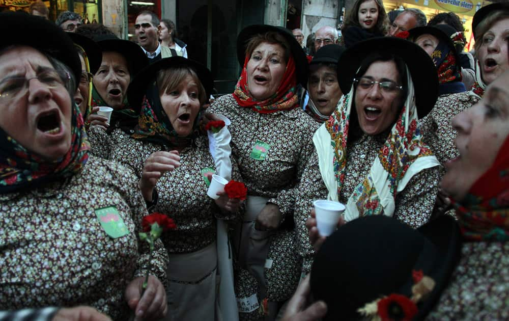 Women dressed in traditional Portuguese clothes sing a song about emigration after a march that celebrated the 40th anniversary of the 25th April revolution that restore the democracy in Portugal in 1974, in Lisbon.