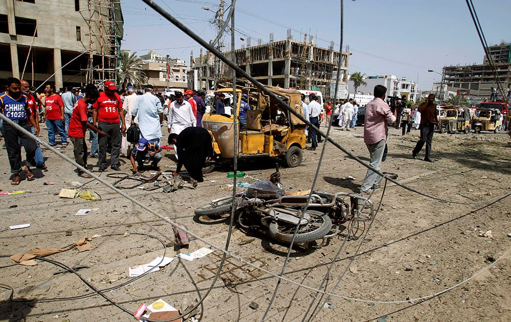 Pakistani officials collect evidence at the site of an explosion in Karachi, Pakistan.