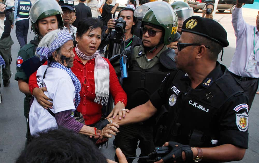 Villagers from Boeung Kak Lake community are stopped by local security guards near a blocked main street near the Phnom Penh Municipality Court during villagers` gathering to call for the release of anti-governments protesters who were arrested in a police crackdown, in Phnom Penh, Cambodia.