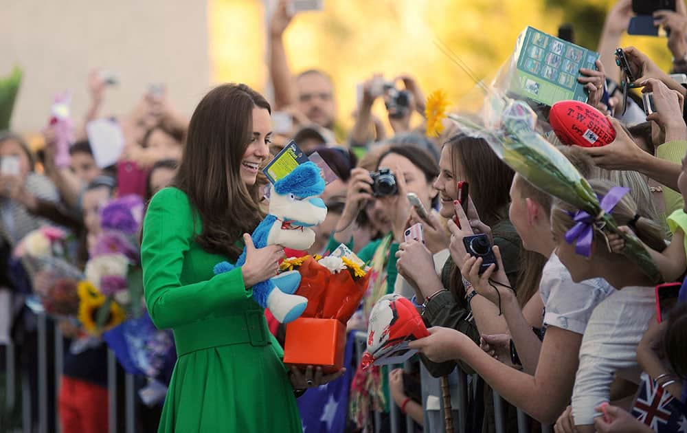 Britain`s Kate, the Duchess of Cambridge, left, meets well-wishers during a visit to the National Portrait Gallery in Canberra.