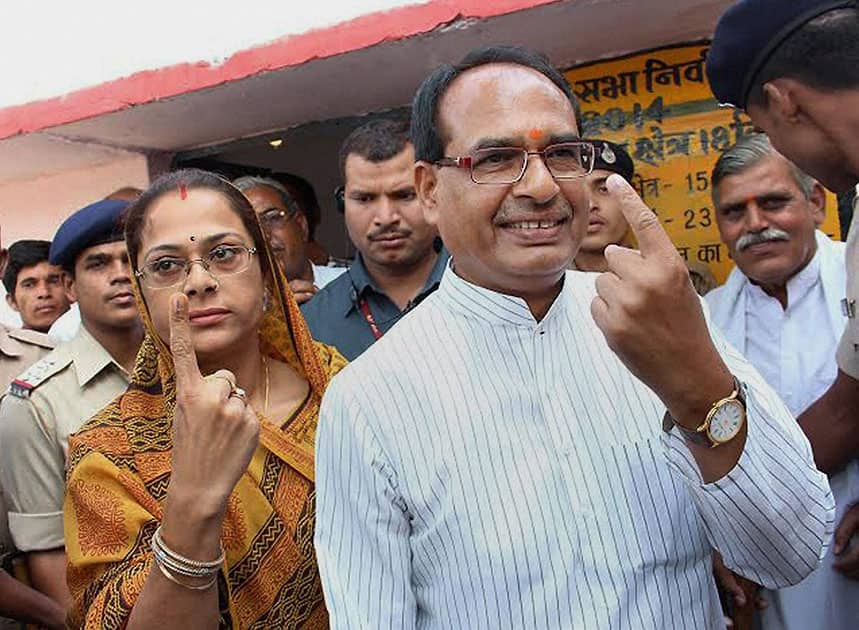 Madhya Pradesh Chief MInister Shivraj Singh Chouhan with his wife Sadhna Singh show their inked fingers after casting votes at a polling booth at his native village Jait, Vidisha in Madhya Pradesh.