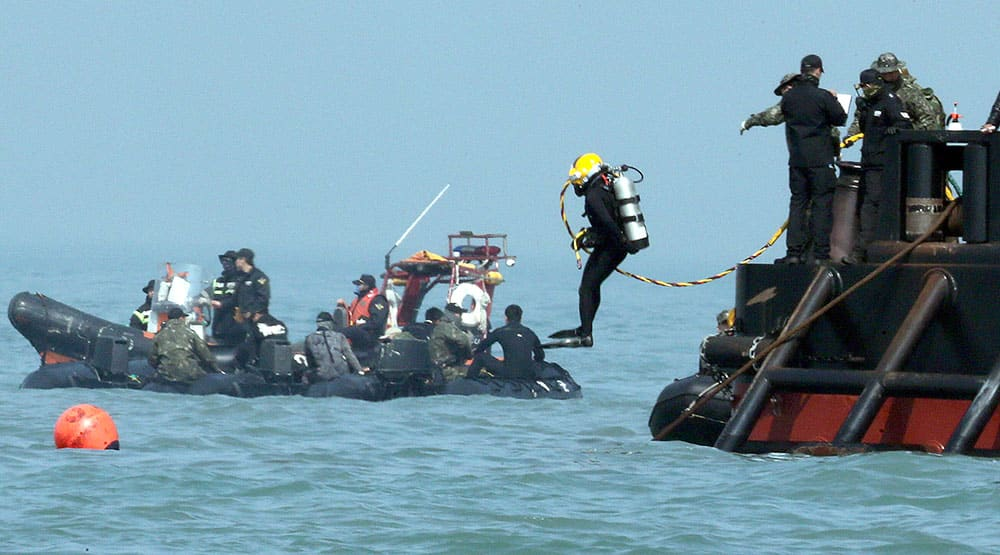 A diver jumps into the sea to look for people believed to have been trapped in the sunken Sewol ferry near buoys which were installed to mark the vessel in the water off the southern coast near Jindo Korea.