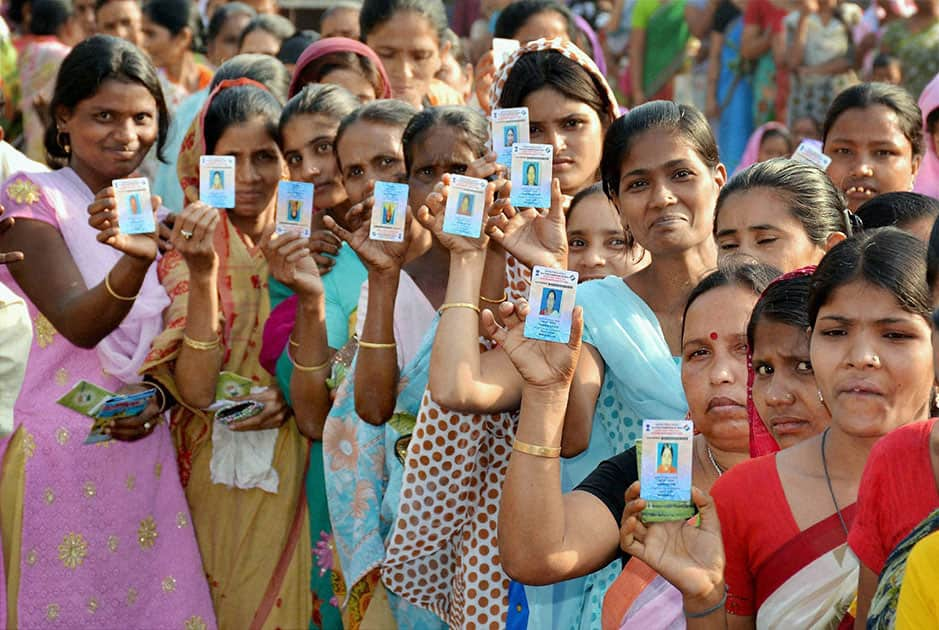 Woman voters show their voter identity cards as they wait in a queue to cast votes for Lok Sabha polls outside a polling station, in Guwahati.
