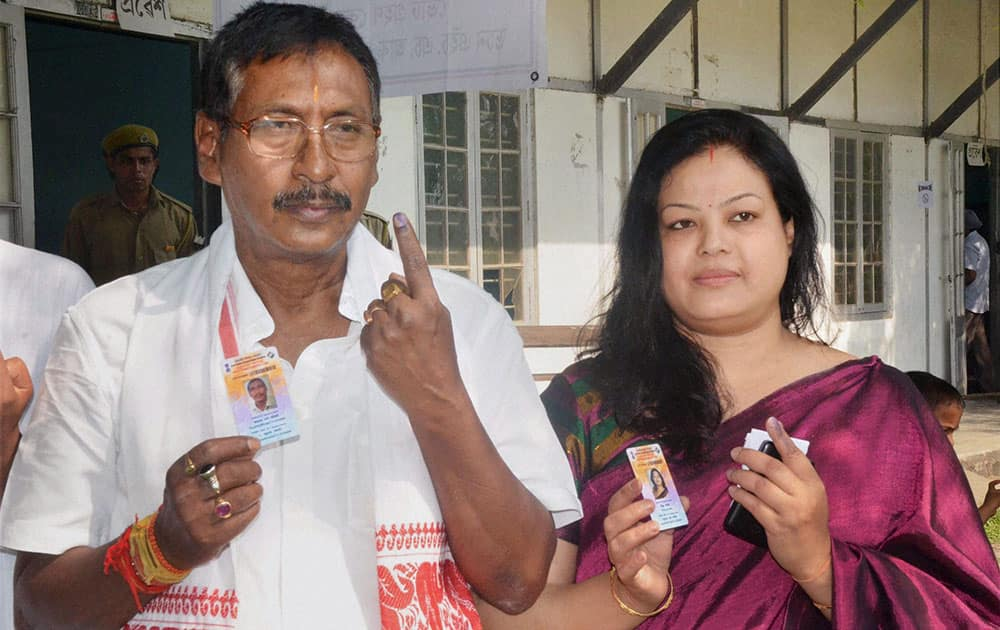 BJP candidate from Nagaon constituency Rajen Gohain with his wife shows their inked fingers after casting their votes for Lok Sabha polls, in Nagaon district of Assam.