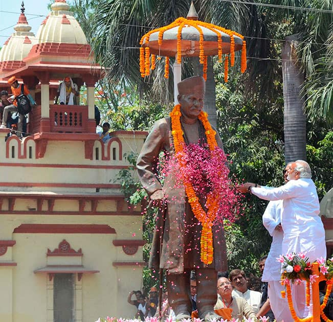 BJP Prime Ministerial candidate Narendra Modi waves at supporters while paying floral tributes to Pt. Madan Mohan Malviya before filing his nomination papers in Varanasi.
