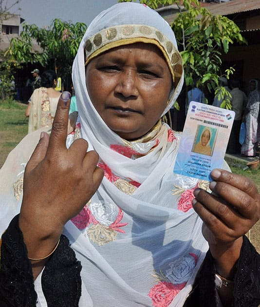 A woman shows her inked finger after casting her vote for Lok Sabha polls at a polling station, in Guwahati.