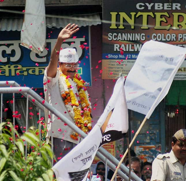 AAP convener Arvind Kejariwal waves to supporters at a roadshow before filing his nomination papers in Varansi.