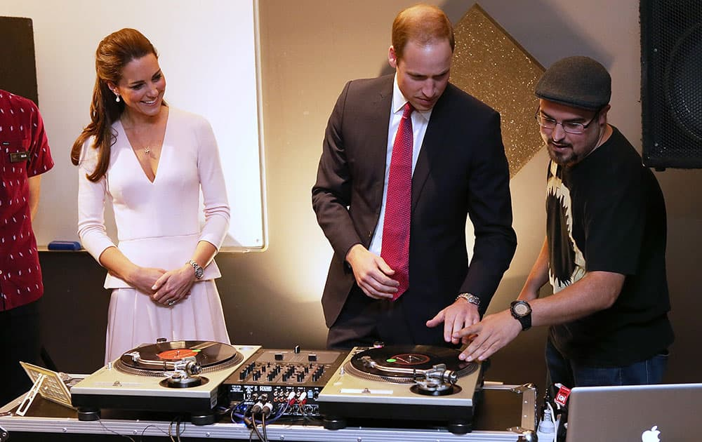 Britain`s Kate, the Duchess of Cambridge, watches as Prince William, center, uses the DJ decks at the youth community center, The Northern Sound System, in the suburb of Elizabeth, in Adelaide, Australia.
