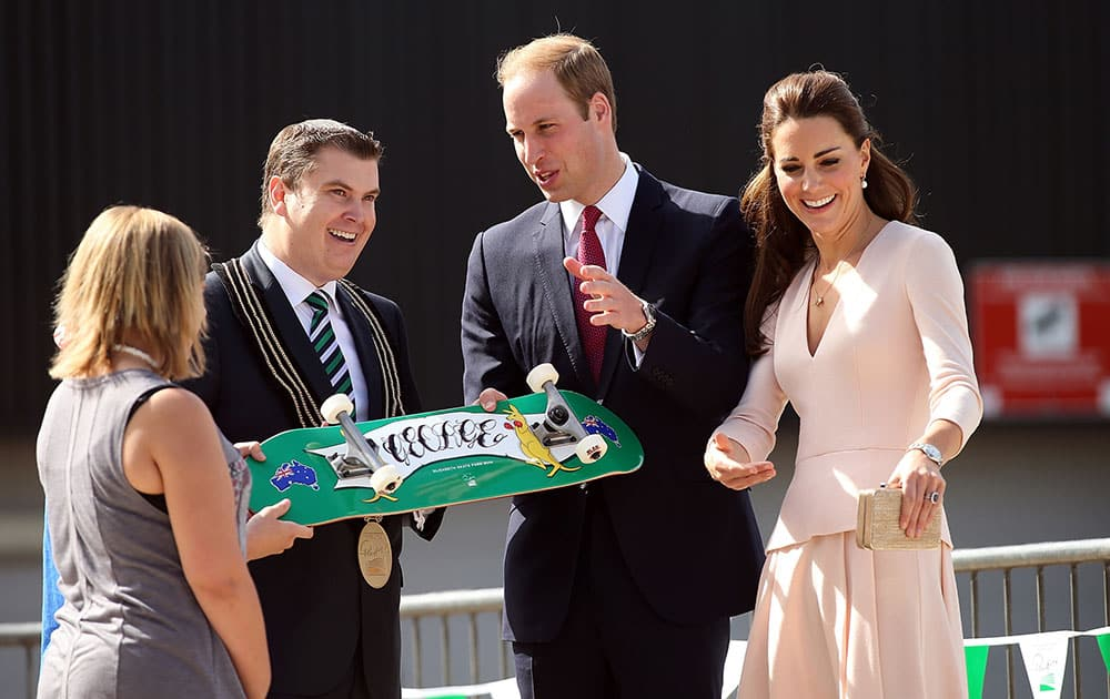Britain`s Prince William, second right, and his wife Kate, the Duchess of Cambridge, right, are given a skateboard by the City of Playford Mayor, Glenn Docherty, second left, during a display at a skate park in the suburb of Elizabeth, in Adelaide, Australia.