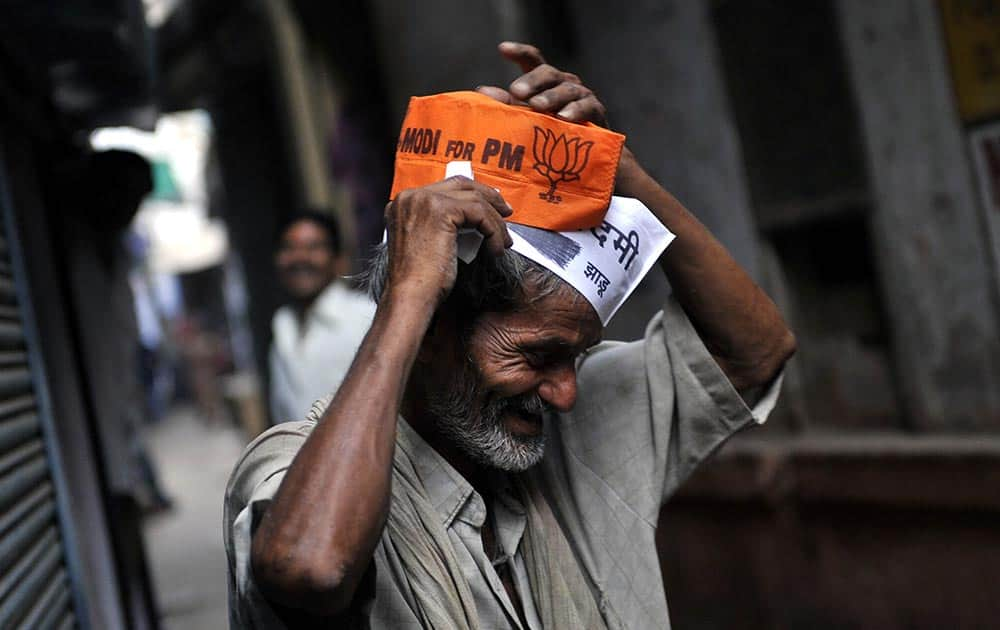 A man wears the AAP and BJP caps in Mumbai.