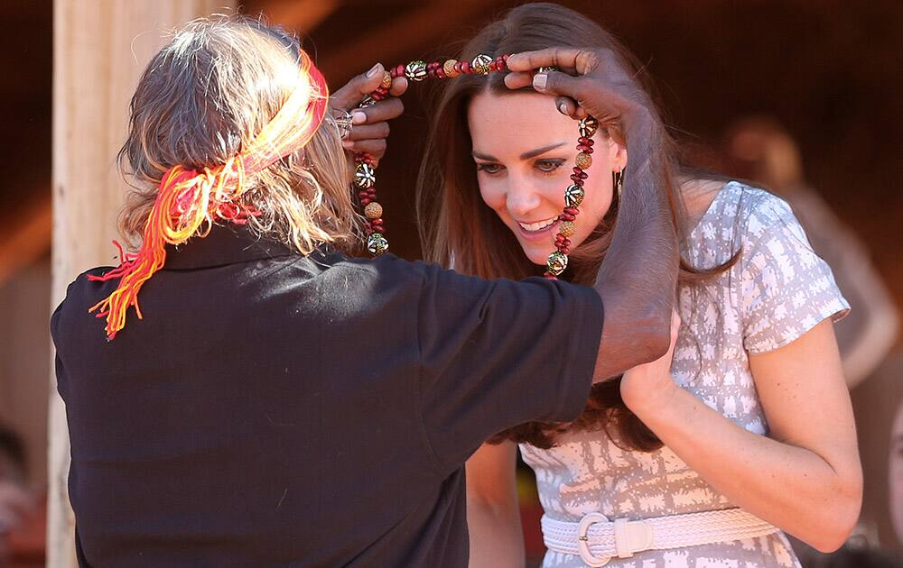 Britain`s Kate, the Duchess of Cambridge, receives a necklace from a local aboriginal woman at the Uluru Cultural center at Uluru, Australia.