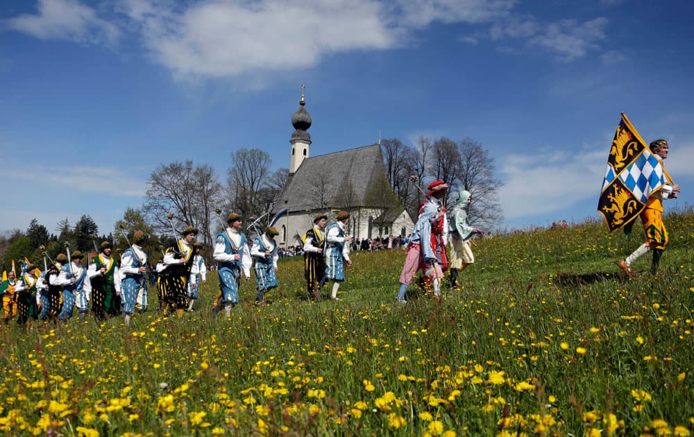 Local residents of the region wearing traditional costumes walk through a meadow to get blessing for men and beasts at the St. George church, in Traunstein, southern German.