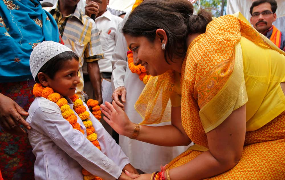 India`s main opposition Bharatiya Janata Party (BJP) candidate Smriti Irani, right, talks to a young Muslim boy at an election rally in Amethi, India.