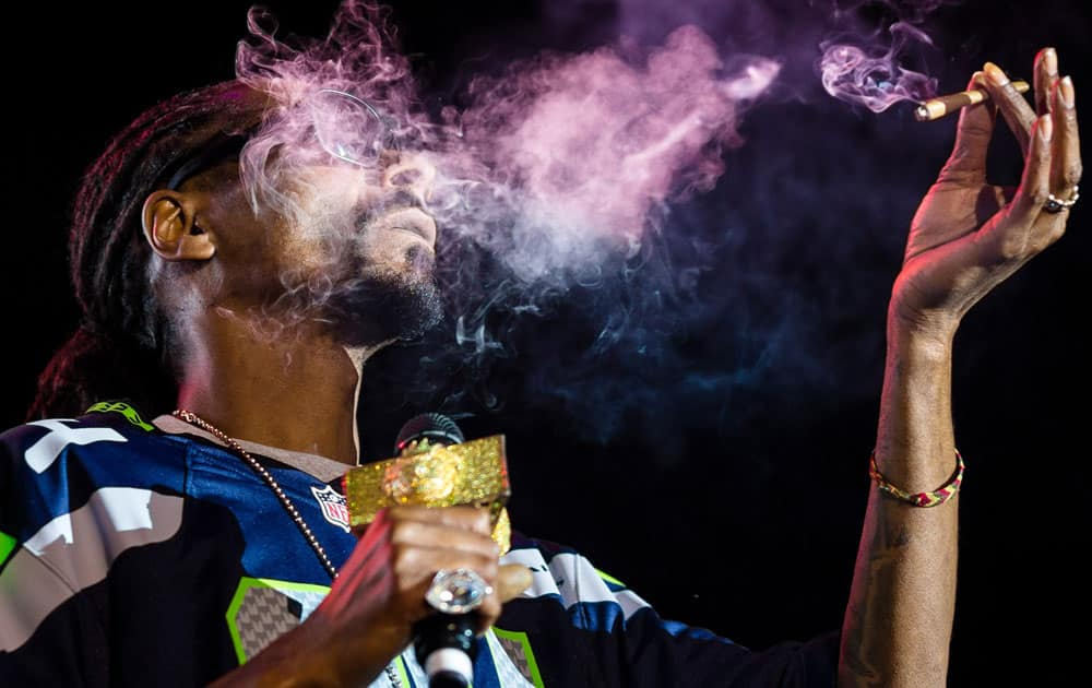 """Snoop Dogg exhales lungfuls of blunt smoke on stage during """"Snoop`s Wellness Retreat"""" tour Saturday. at WaMu Theater in Seattle, Wash."""