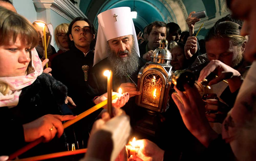 Ukrainian Orthodox believers, lights candles with fire which was delivered to the Ukrainian capital from the Church of the Holy Sepulcher in Jerusalem`s Old City, traditionally believed to be the burial place of Jesus Christ, after the ceremony of the Holy Fire, during the Easter service in the Kyiv-Pechersk Lavra church (Cave Monastery) in Kiev.