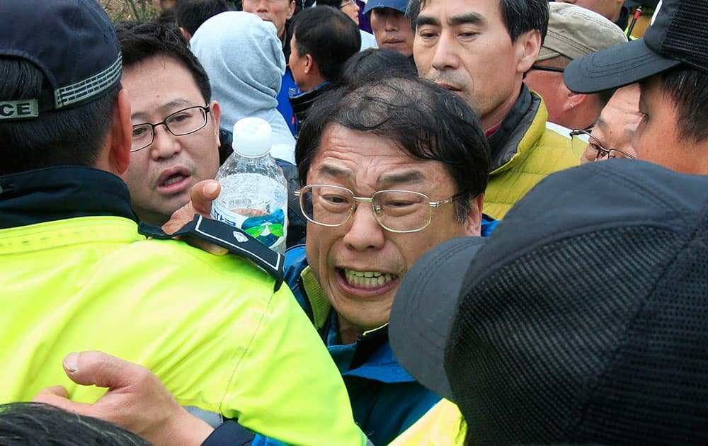 Relatives of missing passengers aboard the sunken ferry Sewol struggle with policemen as they try to march toward the presidential house to protest the government`s rescue operation at a port in Jindo, South Korea.