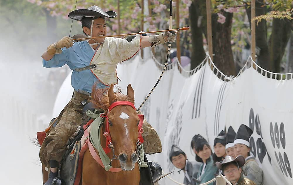 A dressed archer on the horse back prepares to shoot a wooden target in the Asakusa Yabusame horseback archery event at Sumida Park in Tokyo.