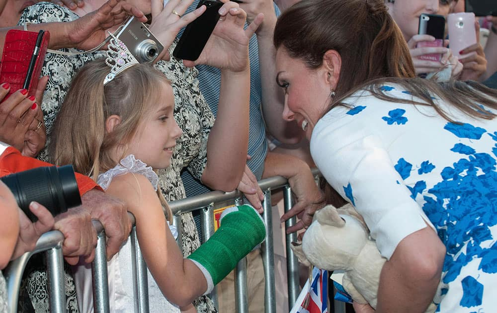 Kate, the Duchess of Cambridge, right, meets a young member of the public after attending a reception at the Brisbane Convention & Exhibition Centre, in Brisbane, Australia.