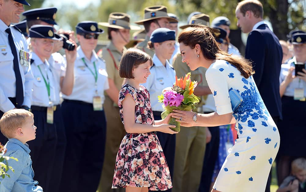Britain`s Kate, the Duchess of Cambridge, receives flowers from Ashleigh Kearnan, 9, during a visit with her husband Prince William, right in background, to RAAF Base Amberley, west of Brisbane, Australia.