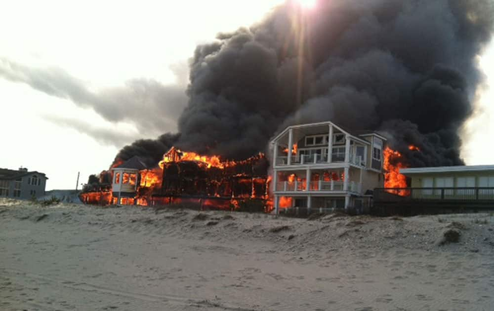 In this photo provided by Joanne Dollarton, fire engulfs three homes near the beachfront, in Sea Isle City, N.J. Authorities say no injuries have been reported in the smoky fire, which erupted around 4:30 p.m. Friday and sent large clouds of black smoke spewing across the region.