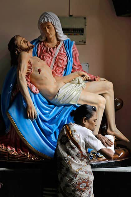 A Catholic woman touches her fractured hand in the belief that it will heal as she stands in front of a portrait of Mother Mary and Jesus Christ on Good Friday in Kolkata.