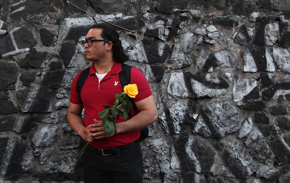 Miguel Guerra, a fan of Colombian author Gabriel Garcia Marquez, stands with flowers outside the funeral home where the body of Garcia Marquez was taken in Mexico City.