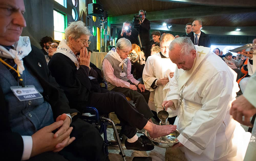 In this picture made available by the Vatican newspaper L` Osservatore Romano, Pope Francis washes the foot of a woman at the Don Gnocchi Foundation Center in Rome.