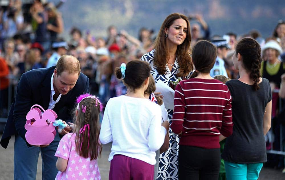 Britain`s Prince William, left, and his wife, Kate, the Duchess of Cambridge, third left, speak with a group of young children during a tour of Echo Point in Katoomba, Australia.