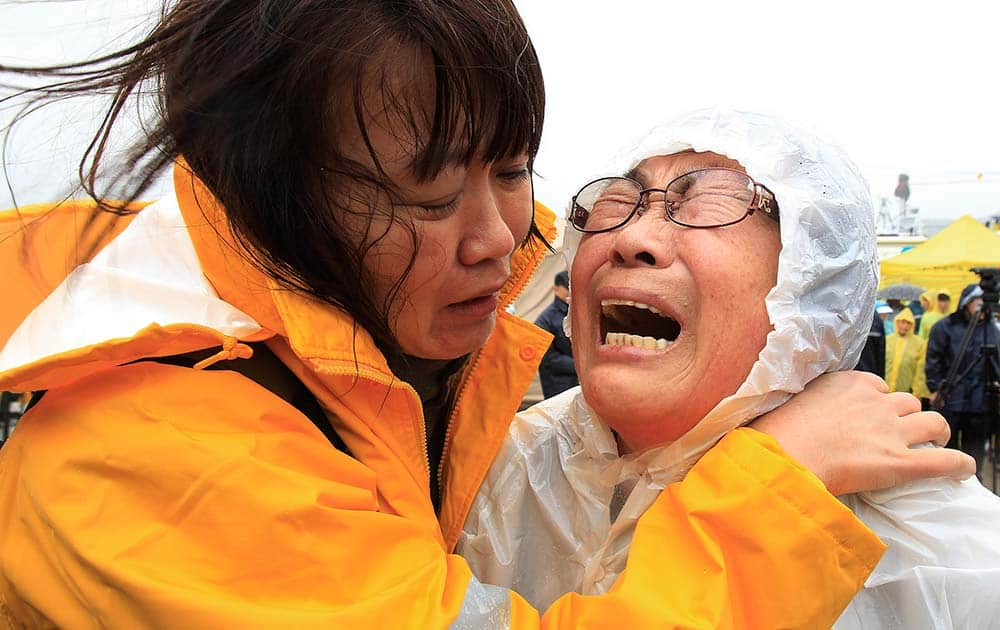 Relatives of a passenger aboard a sunken ferry weep as they wait for the news on the rescue operation, at a port in Jindo, South Korea.