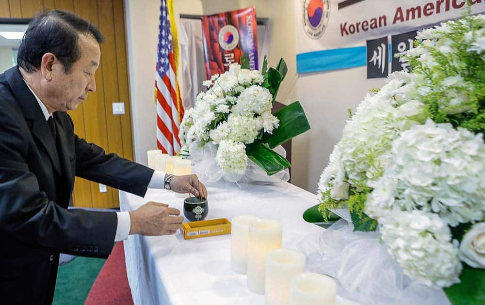 Mon Han Bae, president of the Korean American Federation of Los Angeles, lights incense, during a vigil for victims aboard the sunken South Korean ferry boat, at the Korean Federation of Los Angeles.