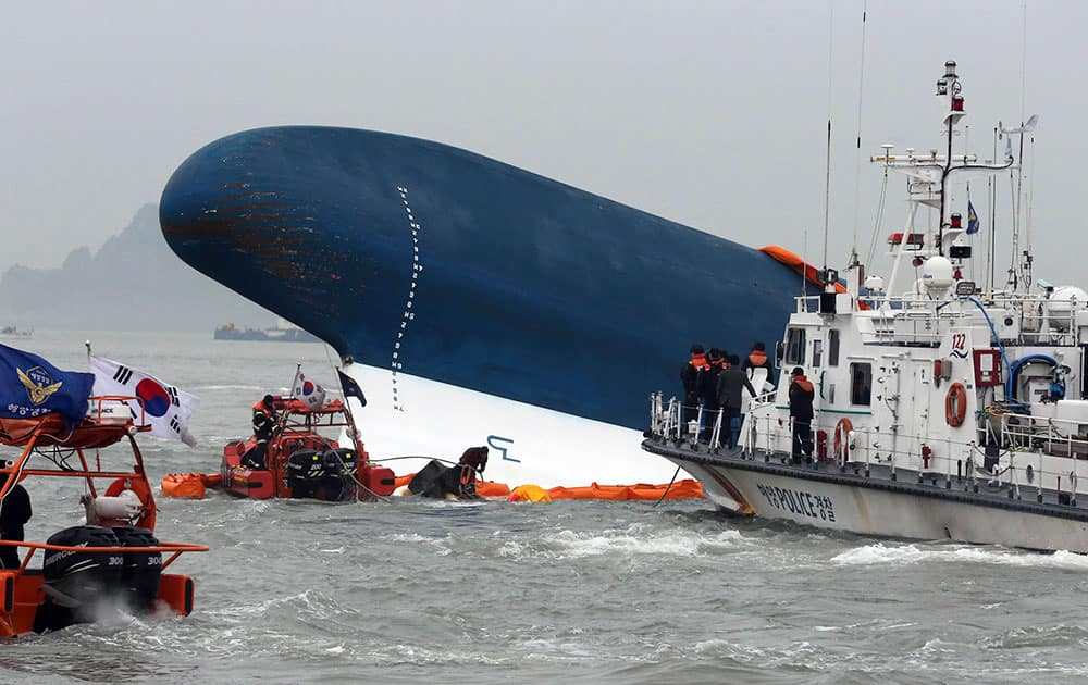 South Korean Coast Guard officers try to rescue missing passengers from a sunken ferry in the water off the southern coast near Jindo, south of Seoul, South Korea.