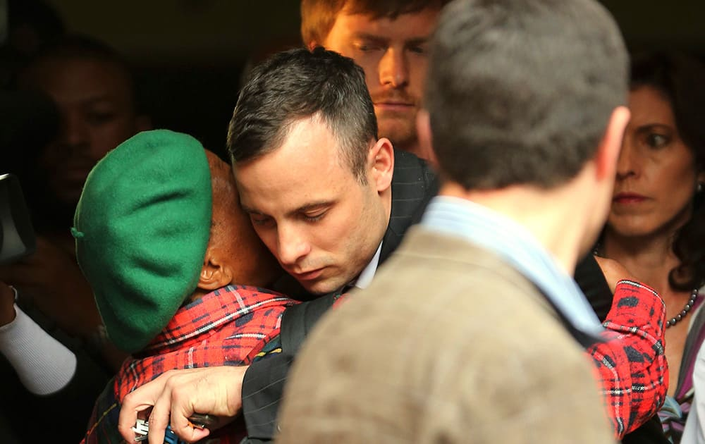 Oscar Pistorius shares a hug with an unidentified woman as he leaves the high court in Pretoria, South Africa.