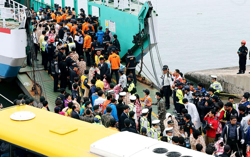 Rescued passengers are escorted by members of a rescue team upon their arrival at a port in Jindo, south of Seoul, South Korea.